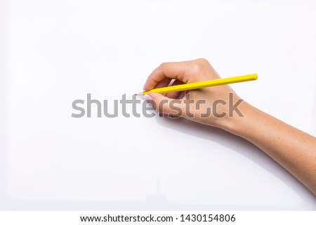 hand holds yellow pencil in blank white background Royalty-Free Stock Photo #1430154806
