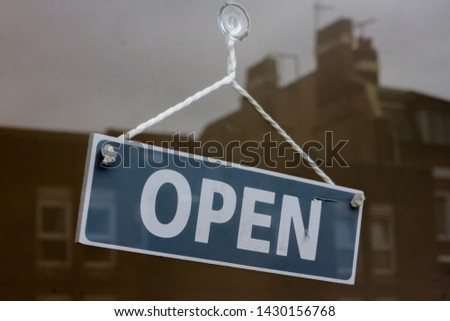 Open sign behind glass slightly crooked or at a diagonal angle with a house reflected in the glass #1430156768