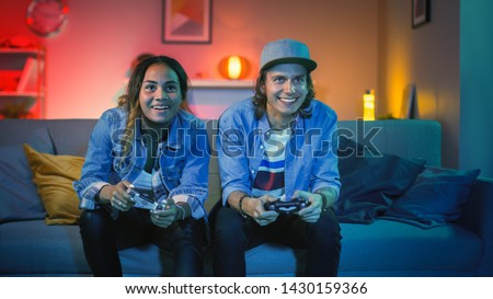 Excited Black Gamer Girl and Young Man Sitting on a Couch and Playing Video Games on Console. They Plays with Wireless Controllers. Cozy Room is Lit with Warm and Neon Light. #1430159366