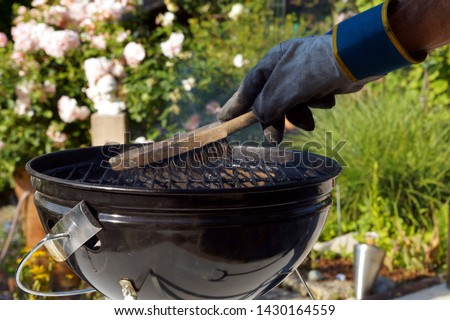 Cleaning a grill. Male hand with gloves cleans round grill with stiff brush. preparation of a grill before cooking. man is cleaning a grill at garden #1430164559
