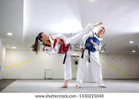 Young woman training martial art of taekwondo with her coach, sportsmanship concept  #1430225048