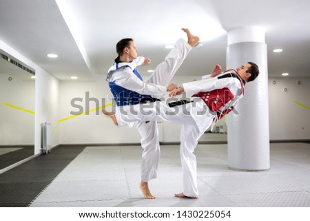 Guys in blue and red protective gear training in clinch, taekwondo concept #1430225054