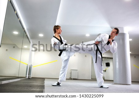 Disabled martial art athlete performing a combat simulation in taekwondo with her coach #1430225099