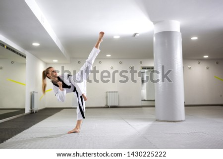 Cute girl with dyed blonde hair practicing martial art of taekwondo, healthy lifestyle concept #1430225222