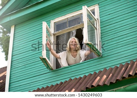 Senior blonde woman opening window inthe morning morning waking up. Active morning at the country side or village. #1430249603