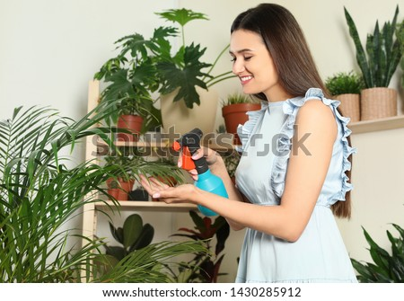 Smiling woman spraying indoor plants at home #1430285912