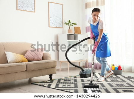 Woman hoovering carpet in living room. Cleaning service Royalty-Free Stock Photo #1430294426