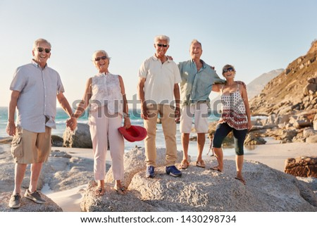 Portrait Of Senior Friends Standing On Rocks By Sea On Summer Group Vacation #1430298734