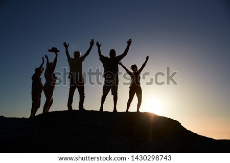 Silhouette Of Senior Friends Standing On Rocks By Sea On Vacation At Sunset With Arms Outstretched #1430298743