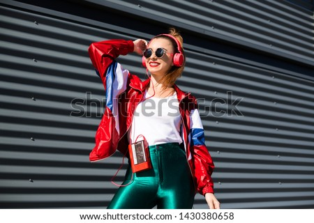 Back in time 90s 80s. Stylish girl in retro jacket and vintage cassette player listens to music, fashion trends, entertainment, heat in summer #1430380658