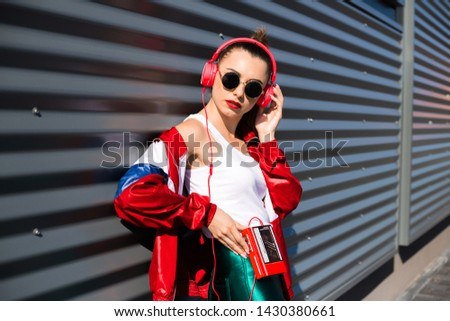 Back in time 90s 80s. Stylish girl in retro jacket and vintage cassette player listens to music, fashion trends, entertainment, heat in summer #1430380661