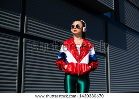 Back in time 90s 80s. Stylish girl in retro jacket and vintage cassette player listens to music, fashion trends, entertainment, heat in summer #1430380670