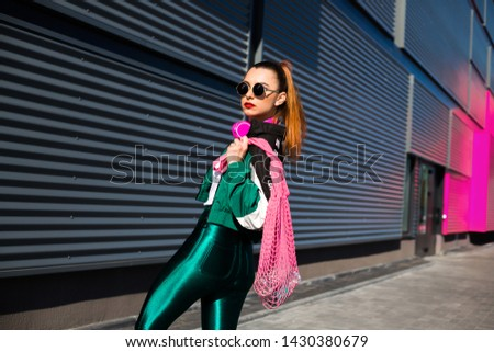 Back in time 90s 80s. Stylish girl in retro jacket and vintage cassette player listens to music, fashion trends, entertainment, heat in summer #1430380679