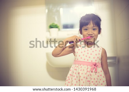 Little cute baby girl cleaning her teeth with toothbrush in the bathroom #1430391968