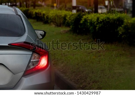 Backside of gray car with drop water on body and open light brake on the road. Beside with green grass and tree for environment. #1430429987