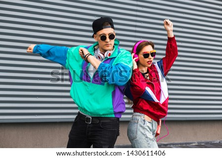 Back in time 90s 80s. Stylish young man in a retro jacket and a girl in red and with a vintage cassette player, against a steel wall, fashion trends, a street image #1430611406