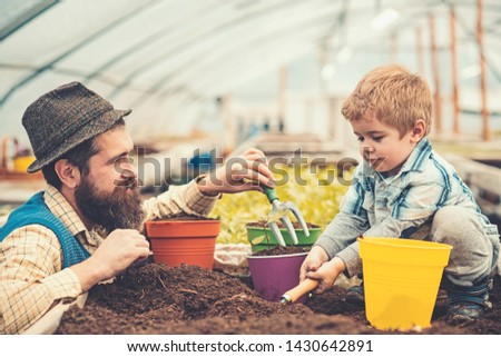 Side view daddy looking at his lovely boy playing with soil. Hipster with stylish beard in fedora hat helping his son. Family spending time out of town. #1430642891