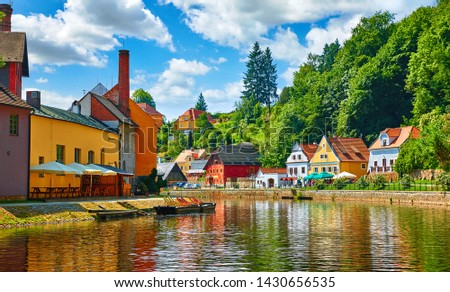 Cesky Krumlov (Czech Krumlov), Czech Republic. Antique town on river Vltava. Picturesque landscape with cosy colourful houses on banks among green trees. Sunny summer day with blue sky and clouds. #1430656535
