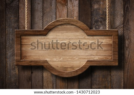 Wooden sign with rounded shape hanging on ropes with wood planks