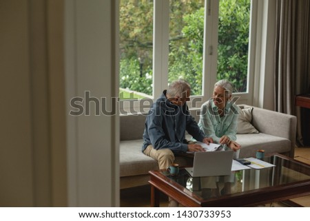 Side view of active senior Caucasian couple calculating bills in living room at home #1430733953