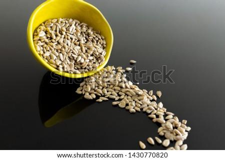 Sunflower seeds spilled on black table. #1430770820