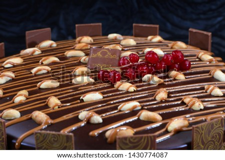 Chocolate cake covered with caramel sauce with cherry cut and sweet nuts #1430774087