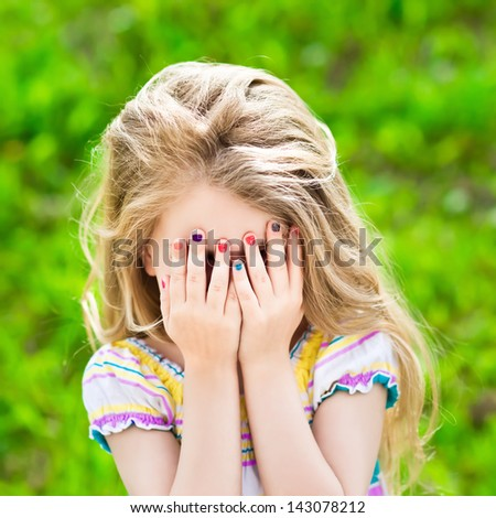 Beautiful little girl with long blond hair and many-coloured manicure covering her eyes with her hands #143078212