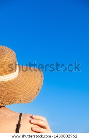 Summer holidays mood: female in beach hat, covered in sand in bright blue background. Shoulders of a young woman in a retro hat, chot from behind #1430802962