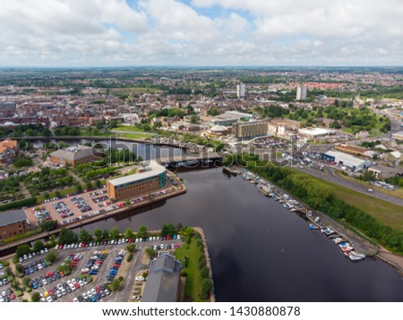 Aerial photo of the UK town of Middlesbrough a large post-industrial town on the south bank of the River Tees in the county of North Yorkshire, taken on a bright sunny day with boats on the river. #1430880878