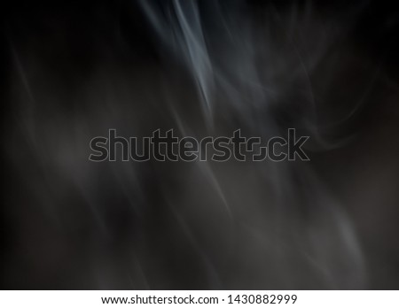 Silky smoke from a burning incense stick on a black background. #1430882999
