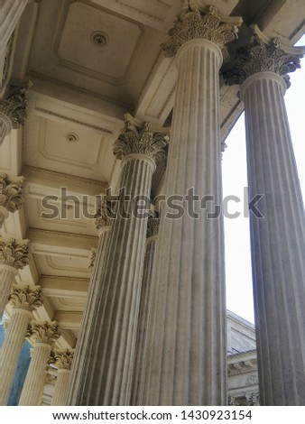 high gray marble columns photographed from the bottom up with stucco on the ceiling #1430923154