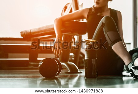 Fitness woman Relaxing after exercise with a whey protein and dumbbell placed beside the gym.Relaxing after training.beautiful young woman looking away while sitting  at gym. #1430971868