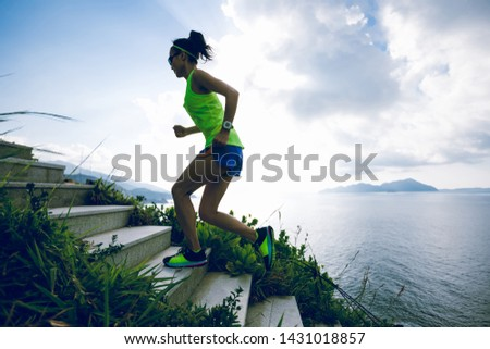 Determined woman running up on seaside mountain stairs #1431018857