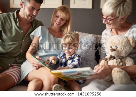Family with daughter and grandma looking picture book