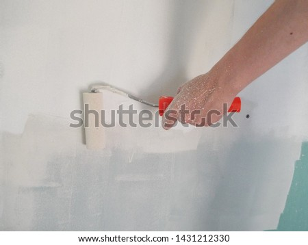 priming the walls with a roller in the repair of the house #1431212330