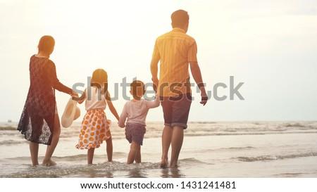 Happy asian family enjoying walk on the beach #1431241481