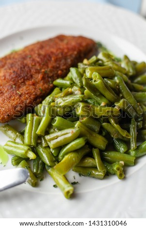 Close up of deep fried chicken schnitzel with crunchy crust and steamed green beans for a nutritious lunch #1431310046