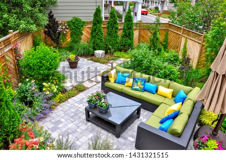 A beautiful small, urban backyard garden featuring a tumbled paver patio, flagstone stepping stones, and a variety of trees, shrubs and perennials add colour and year round interest. #1431321515