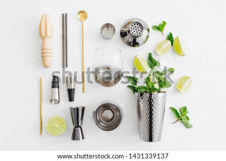 Set of bar accessories for cocktail making. Shaker, jigger, glass, spoon  and  other bar tools with lime and mint leaves on withe  background.  #1431339137