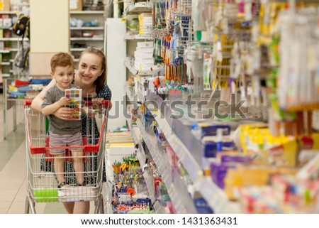 Kyiv, Ukraine- May 15, 2019 Mother riding their child in shopping trolley at school stationery store. Elementary school and education #1431363431
