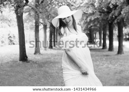 Pregnancy, love, people and expectation concept - happy pregnant woman posing over green natural background in white dress and hat, and dancing. Black and white photo. #1431434966