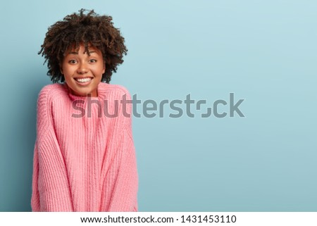 Positive dark haired female gazes happily with tender smile, dressed in oversized rosy sweater, pleased to hear pleasant words of praise, models in studio against blue background. Emotions concept #1431453110