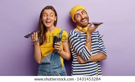 Indoor view of happy woman and man keep modern cell phones near mouthes, make voice call, enjoy nice conversation, drink hot beverage from disposable cup, stand back to each other over purple wall Royalty-Free Stock Photo #1431453284