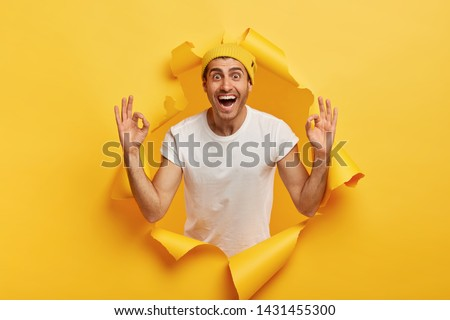 Everything is under control. Delighted happy man gives positive opinion, makes okay gesture with both hands, says excellent choice, poses in torn paper hole. Ok, got it. Good excellent idea.