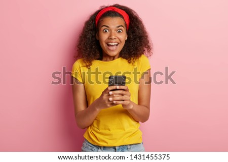 Indoor shot of amused beautiful young African American lady enjoys using new brand gadget, connected with world everywhere, has charming smile, wears yellow t shirt, models on pink background #1431455375