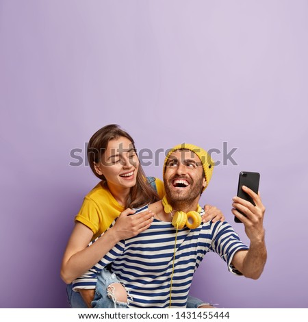 Funny young couple take selfie on smartphone, enjoy piggyback ride, have happy expressions, lovely woman hugs boyfriend from back, isolated over violet background. People, fun, leisure time concept #1431455444