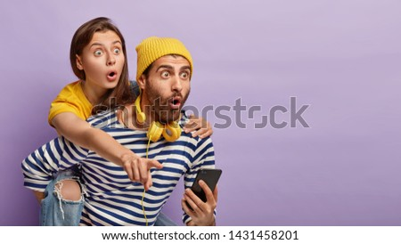 Surprised male gives piggyback to woman who points finger into distance, hold smartphone device, listen music from palylist, stare with bugged eyes, isolated on purple background with free space #1431458201