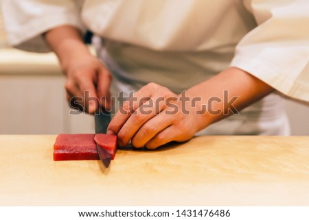 Japanese Omakase Chef cut bluefin tuna (Otoro in Japanese) neatly by knife on wooden kitchen counter for making sushi. Japanese luxury meal. #1431476486