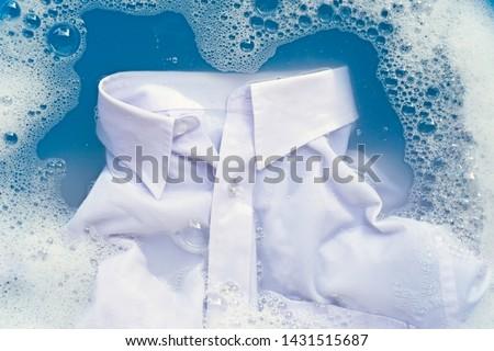 White shirt soak in powder detergent water dissolution, washing cloth. Laundry concept #1431515687