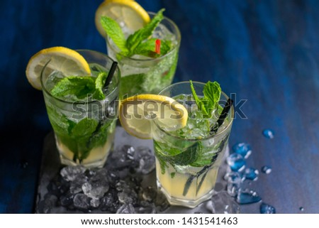 three glasses of mojito cocktail with fresh lemon and peppermint on a black stone board with ice #1431541463